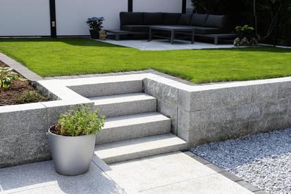Gepflegter Ziergarten mit Granitmauer und Blockstufentreppe